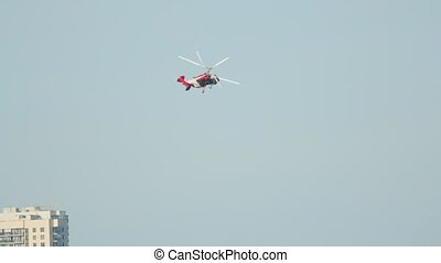Red-white helicopter turns against a city park with a ferris...