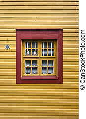 Red window on a yellow wall