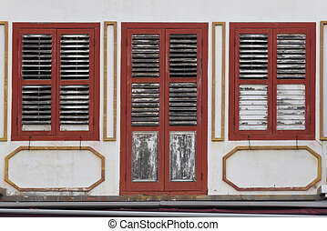 Red windows with shutters on white wall