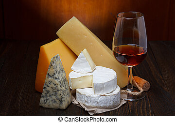 Red wine and cheese assortment on wooden table