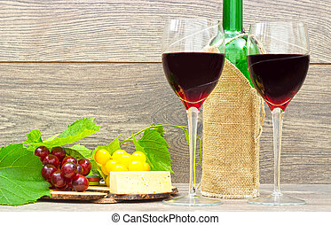 red wine and fruits on wooden background