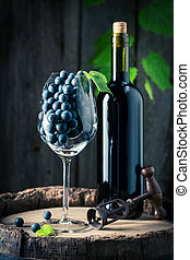 Red wine and grapes on old barrel