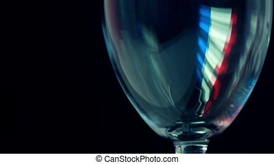 Red wine being pored into wineglass with French flag-like...
