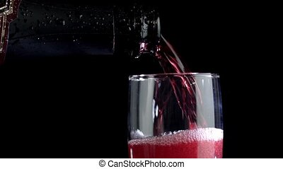 Red wine being poured into a glass of black background. Slow motion