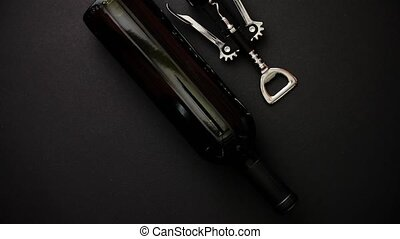 Red wine bottle and corkscrew on black matte background. Top...