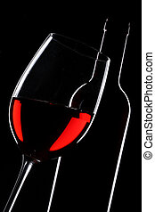 Red wine bottle and glass silhouette over black background