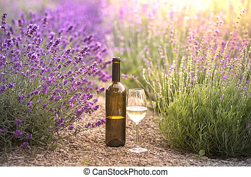 Red wine bottle and wine glass on the ground. Bottle of wine against lavender landscape. Sunset over a summer lavender field in Provence, France