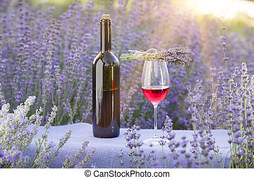 Red wine bottle and wine glass on the table. Bottle of wine against lavender landscape. Sunset over a summer lavender field in Provence, France