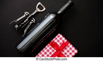 Red wine bottle, corkscrew and boxed christmas gift on black...