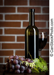 Red wine bottle on brick wall background