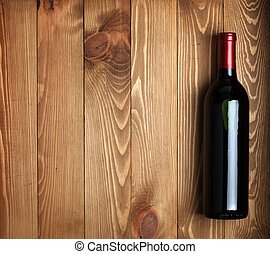 Red wine bottle on wooden table background