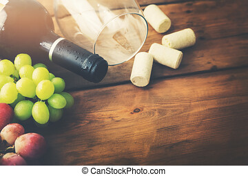 red wine bottle with glass and grapes on wooden background
