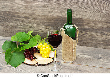 red wine, cheese and grapes on a wooden background