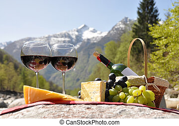 Red wine, cheese and grapes served at a picnic. Verzasca ...