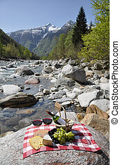 Red wine, cheese and grapes served at a picnic. Verzasca...