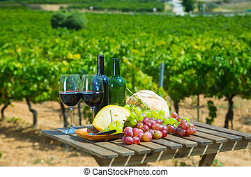 Red wine, cheese, bread on wooden table