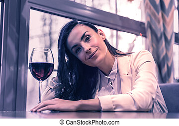 Delighted positive woman drinking a glass of wine