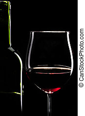 Red wine glass and bottle infront of black background