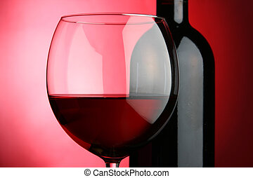 Red wine - Glass and bottle of wine over red background