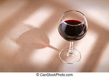 Red wine glass on the table with window shadow