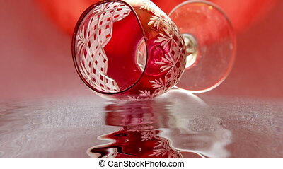 Red wine glass reflects in the water