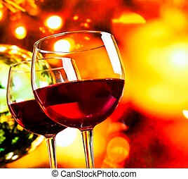 red wine glasses against colorful unfocused lights background