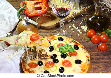 Red wine in a transparent glass and a pizza piece on a wooden sh