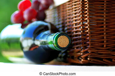 red wine in bottle and basket of grape