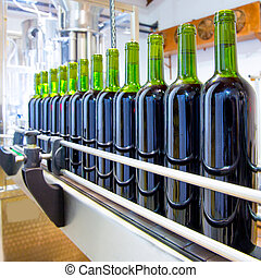 red wine in bottling machine at winery