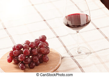 Red Wine in Glass with Grapes on The Table
