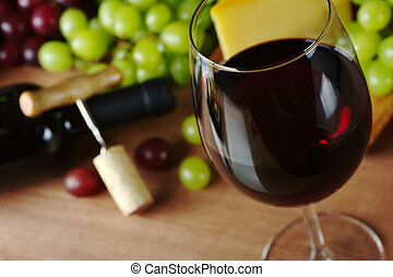 Red wine in wine glass with grapes, cheese a wine bottle and...