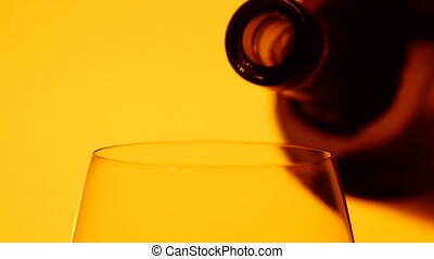 Red wine is being poured into a glass, yellow, closeup,...