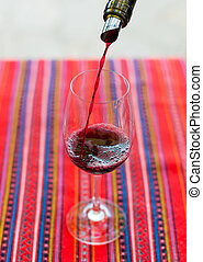 Red wine is pouring into wine glass.