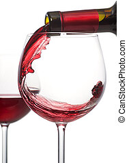 A glass of red wine being poured from a bottle.