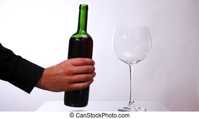 Red wine poured from bottle into glass