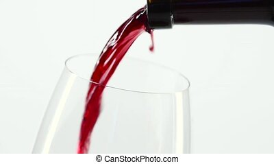 Red wine poured in a glass isolated, white, slowmotion, closeup