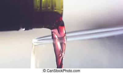 Red wine poured into a glass in slow motion and macro....