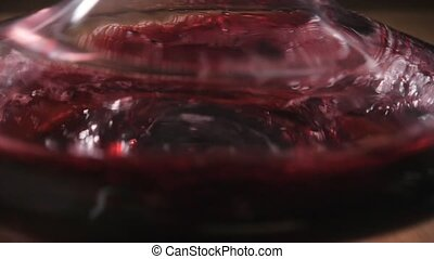 Red wine poured into decanter on restaurant background....
