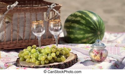 Red wine pouring in crystal glasses on picnic