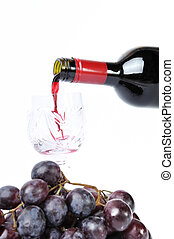 Red wine pouring in the goblet and grapes isolated in white