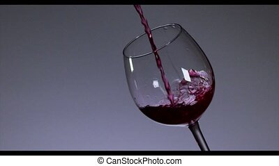 Red wine pouring in wine glass over dark background. 4K,...