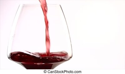 Red wine pouring into a glass, slow motion on white...