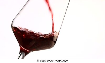 Red wine pouring into a glass, slow motion on white background