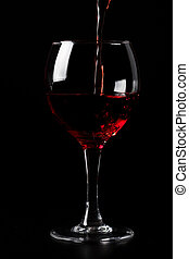 red wine pouring into glass over black background
