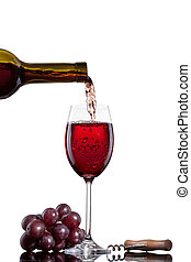 Red wine pouring into glass with grape isolated on white