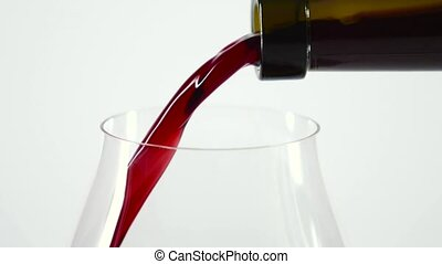 Red wine pouring into wine glass, white, slowmotion, closeup