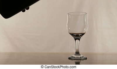 Red wine pouring - Red wine being poured into wine glass on...