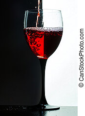 Red wine pouring. white on black background