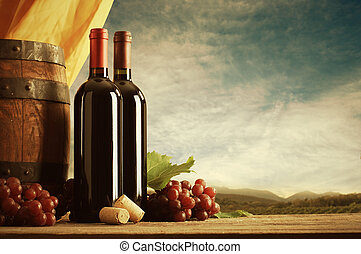 Red wine bottles with barrel and grapes, vineyard on background
