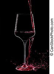 Red wine splashing in a glass.